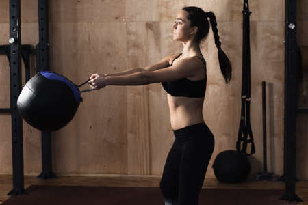 25 29 years: Woman lift weight ball at the gym Stock Photo