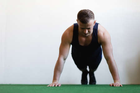 30 34 years: The athlete doing push-up in gym Stock Photo