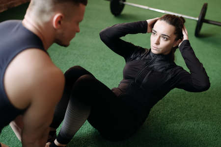 25 29 years: Woman doing sit-ups while a young man steadies her feet Stock Photo
