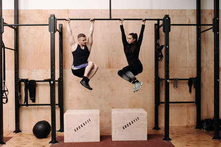and the horizontal man: Man and woman doing exercise on horizontal bar