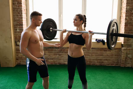 25 29 years: Trainer spotting a woman while shes exercising with weight
