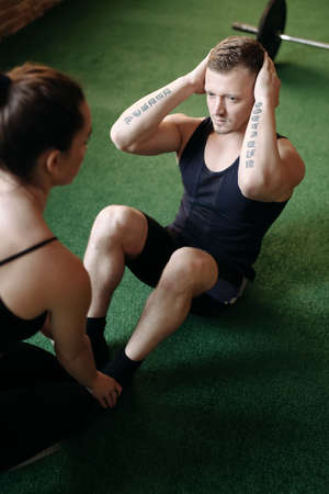 25 29: Man doing sit-ups while a young woman steadies her feet Stock Photo