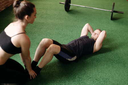 25 29 years: Man doing sit-ups while a young woman steadies her feet Stock Photo