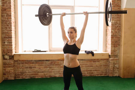 25 29 years: Young woman doing exercising with weight
