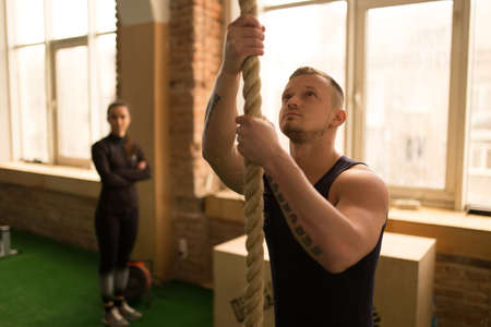 30 34 years: Man climbing rope in gym Stock Photo