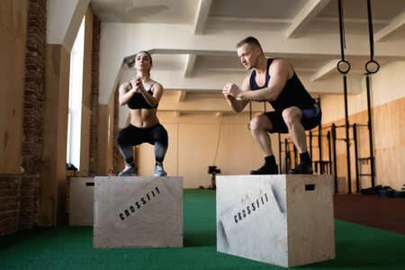 25 30 years women: Man and woman jumping on boxes during crossfit