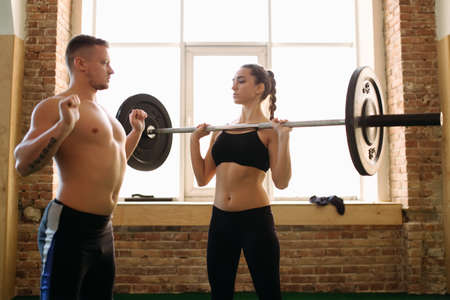25 29 years: Young woman doing exercising with weight while her trainer looks on