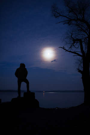 placidity: Moonlight man silhouette. He looks at the moon.