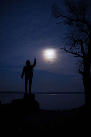 man in the moon: Moonlight man silhouette. He shoot moon on a mobile camera. Stock Photo