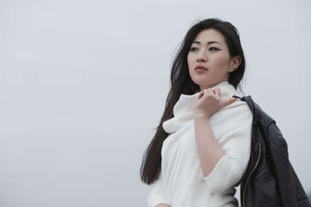 25 29 years: Asian woman holding jacket on cloudy sky background Stock Photo