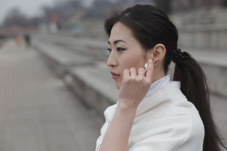 25 29: Asian woman listen music with earphones at embankment