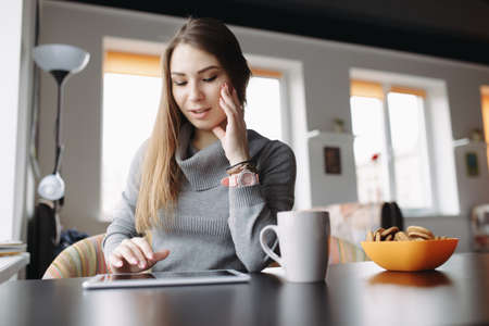 25 29 years: A beautiful young woman using her tablet at coffee shop Stock Photo