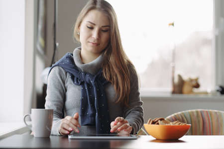 25 29: A beautiful young woman using her tablet at coffee shop Stock Photo