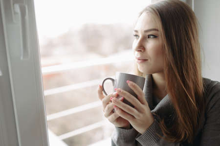 25 29: Attractive young woman sitting in a coffee shop at window