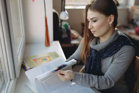 25 29 years: Woman leaf through a journal at the window Stock Photo