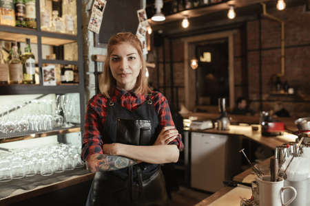 Portret van jonge aantrekkelijke vrouw barman op staaf