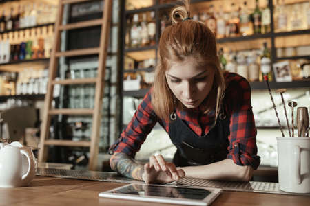 informal clothing: Female barista looking at something on a touchscreen