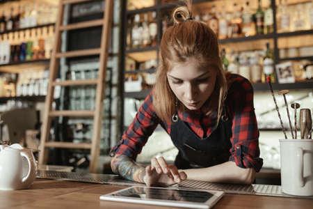 Vrouwelijke barista die iets op een touchscreen bekijkt