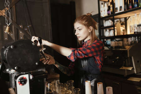 pouring beer: Female bartender pouring beer from faucet at bar