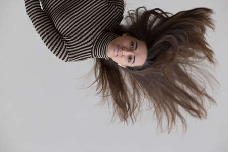 flipped: Flipped over beautiful young woman tossing her hair on gray background Stock Photo