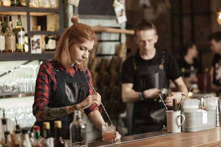 bartenders: Two bartenders working on bar Stock Photo