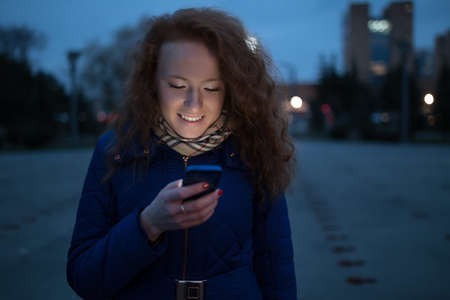 frizz: Smiling young woman using her mobile phone in evening city Stock Photo