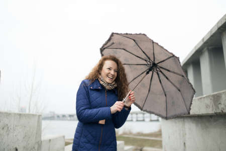 frizz: Smiling pretty woman holding umbrella and walking in city