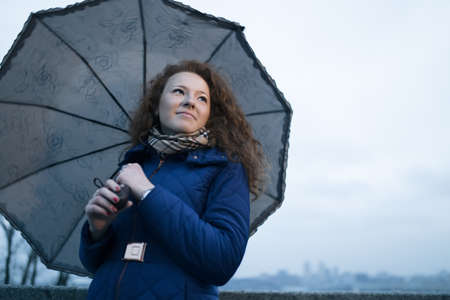 frizz: Young woman under umbrella at cloudy sky background