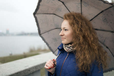 frizz: Young woman walking at quay with umbrella on a rainy day Stock Photo