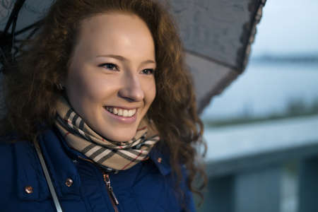 frizz: Young woman under umbrella on a rainy day in evening