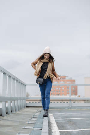 balances: Funny girl goes on thin girder and balances on the roof Stock Photo