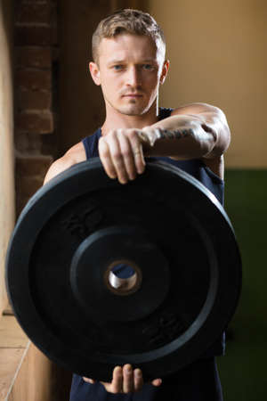 well build: Man doing crossfit exercise with weight disc in gym. Stock Photo