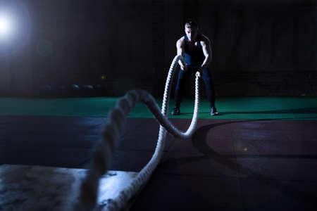 Atletische man doet wat CrossFit oefeningen met een touw in de sportschool Stockfoto