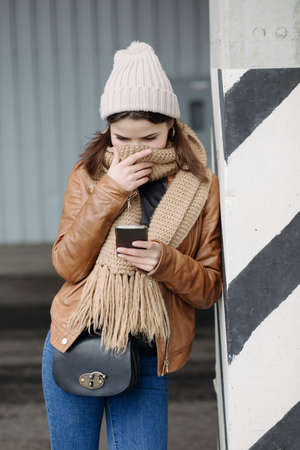 to get warm: Cute girl using her mobile phone at open air parking
