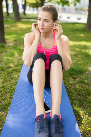 Young sporty woman listen music sitting on grass