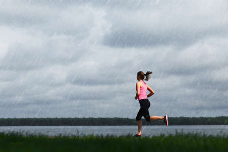 cloudy day: Young sporty woman running at rainy day
