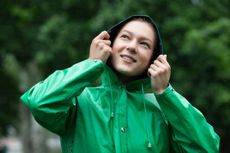 rain wet: Young woman in raincoat holding hood Stock Photo