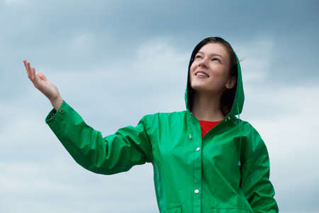 rain wet: Woman in raincoat at overcast sky background