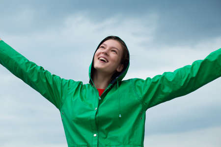 overcast: Woman in raincoat at overcast sky background