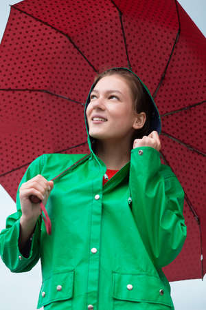 overcast: Woman in raincoat holding umbrella at overcast sky background