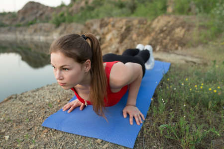 push ups: Young sporty woman doing push ups at the edge of cliff