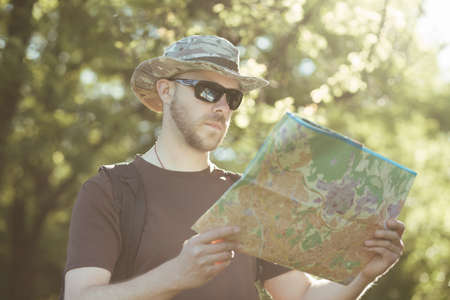 Male explorer looking at a map outdoors