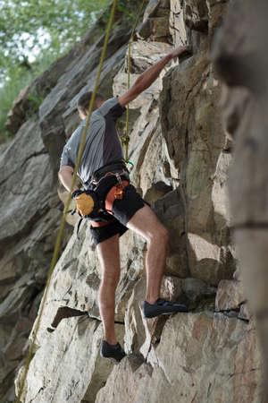 tenacious: Male rock climber climbing a stone structure