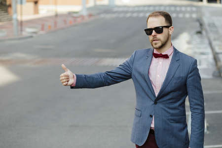 hailing: Handsome businessman hailing a cab in the city Stock Photo