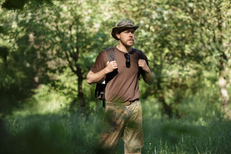 walking alone: Male tourist walking alone in forest Stock Photo