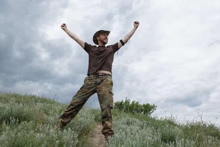 manos levantadas al cielo: �xito del hombre levant� las manos en el campo en el fondo del cielo cambiante