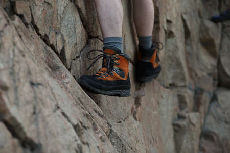 tenacious: Legs of male rock climber clings to a cliff Stock Photo