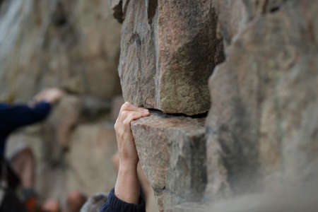 tenacious: Hand of male rock climber clings to a cliff Stock Photo