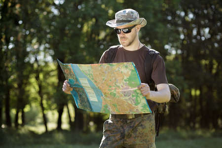 Male tourist looking at a map outdoors