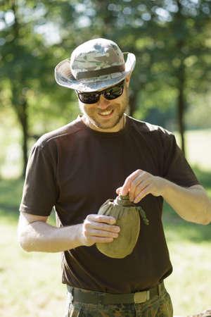 sediento: Hiking concept. Thirsty man having break drinking a flask of water. Foto de archivo